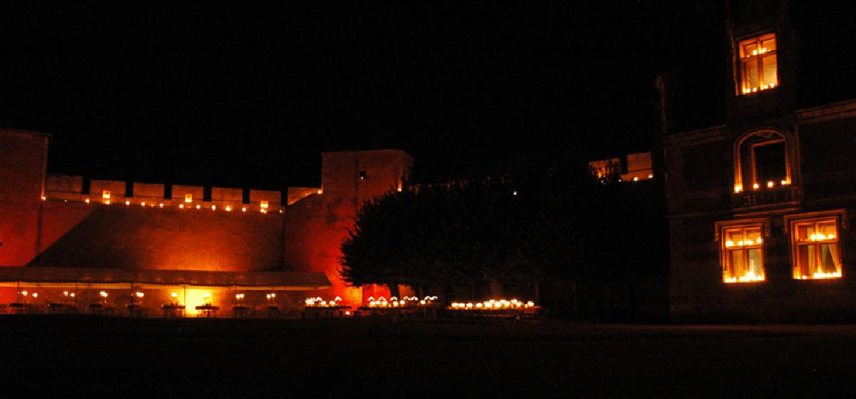 le château d'Ainay-le-Vieil illuminé aux chandelles pour le dîner du Festival de Musique les 72 heures d'août