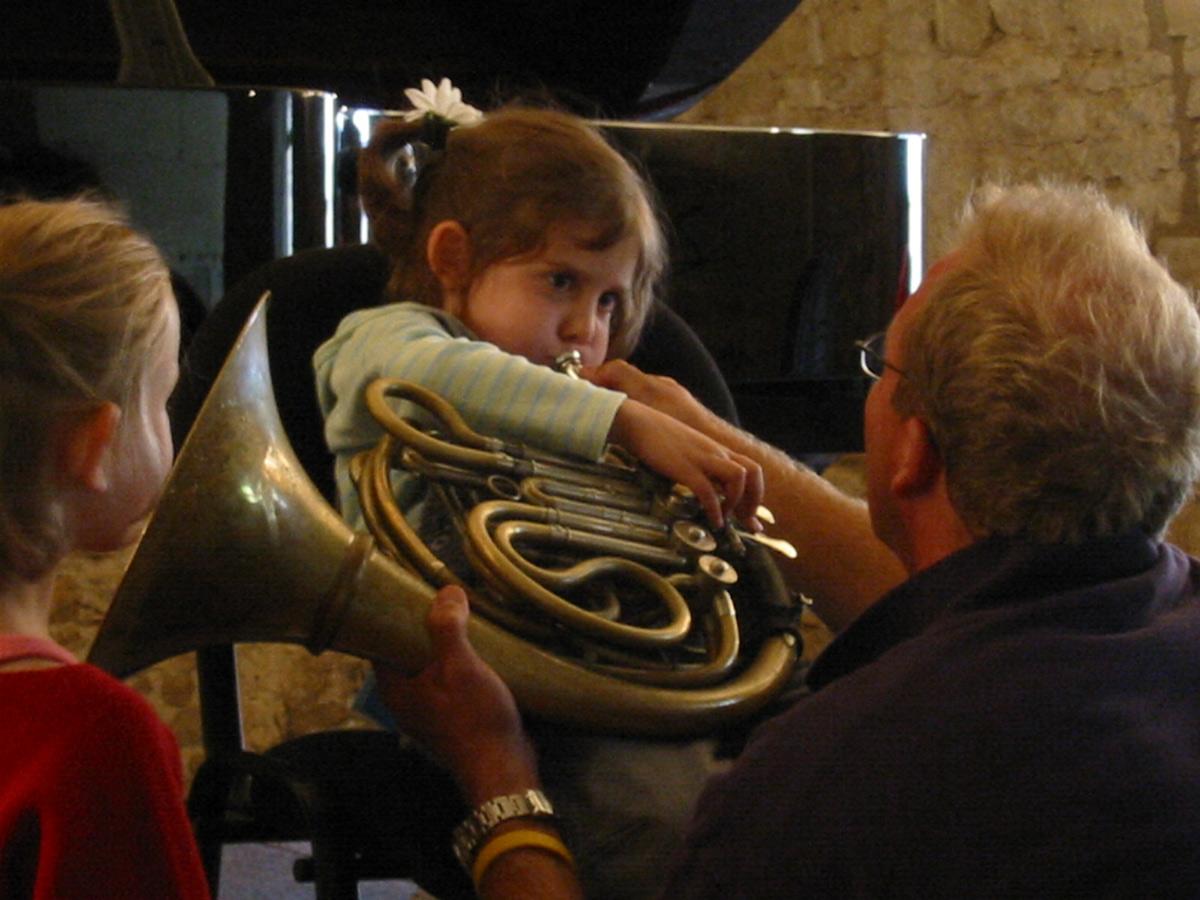 enfant découvrant l'instrument lors du Festival de Musique les 72 Heures d'août à Ainay-le-Vieil