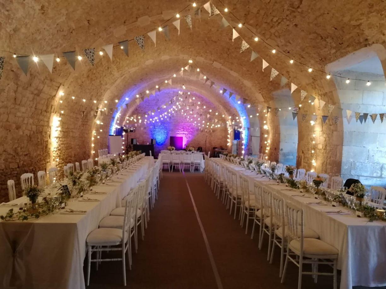 Château d'Ainay-le-Vieil salle des archers avec longues tables de réception guirlandes lumineuses mariage