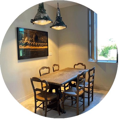 Gîtes du château d'Ainay-le-Vieil, une salle à manger avec une table en bois entourée de chaises paillées éclirée par deux lampes industrielles