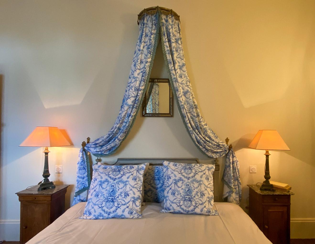 Château d'Ainay-le-Vieil, les chambres d'hôtes, la Chambre Empire, vue sur le lit double avec baldaquin et chevets éclairés