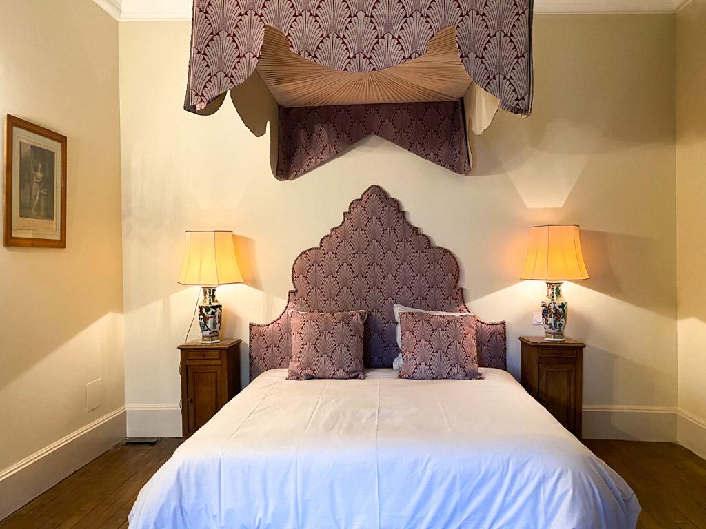 Château d'Ainay-le-Vieil, les chambres d'hôtes, la Chambre Tourzel, vue du lit avec la baldaquin tendu de jacquard bordeaux avec chevets allumés