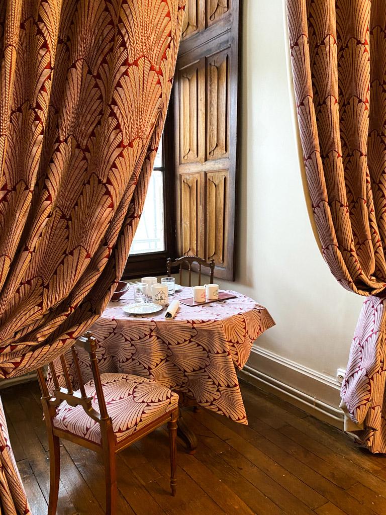 Château d'Ainay-le-Vieil, les chambres d'hôtes, la Chambre Tourzel, vvue de l'alcove avec volets intérieurs à plis de serviette et table de petit-déjeuner