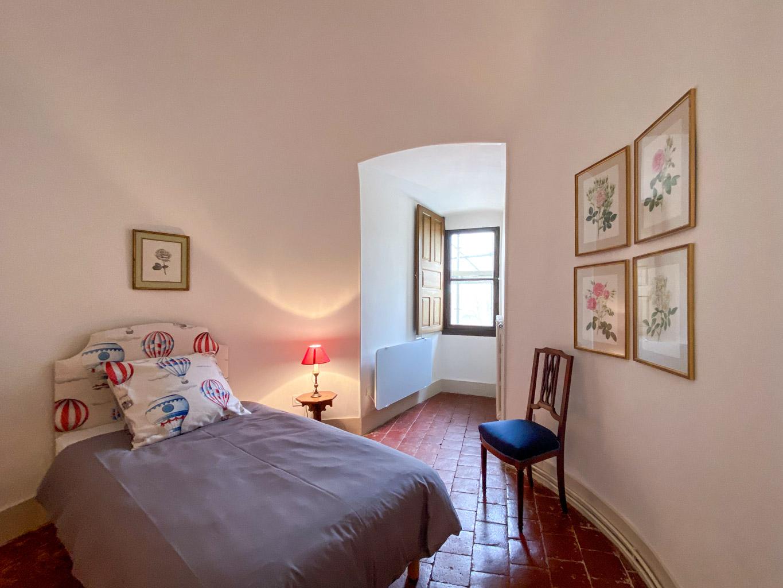 Château d'Ainay-le-Vieil, les chambres d'hôtes, la Suite Bigny, vue sur la chambre avec lits simples, fenêtre donnant sur cour intérieure, gravures de fleurs anciennes encadrées