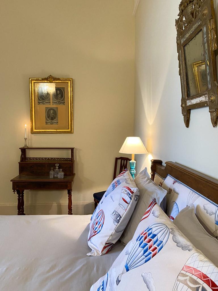 Château d'Ainay-le-Vieil, les chambres d'hôtes, la Suite Bigny, vue sur le lit double avec coussins décoratifs à motifs de montgolfières, chevets éclairés et bureau avec cadres dorés