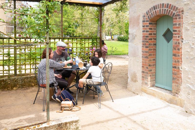 Château d'Ainay-le-Vieil, une famille est attablée autour d'une table de jardin en métal pour déjeuner