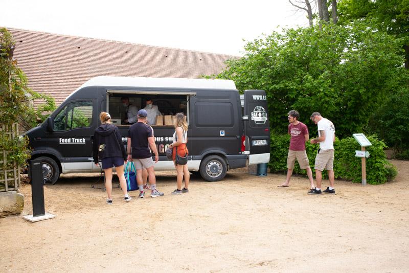 Au Château d'Ainay-Le-Vieil, près de la volière, des visiteurs commandent leur panier-pique-nique au camion de Food Truck