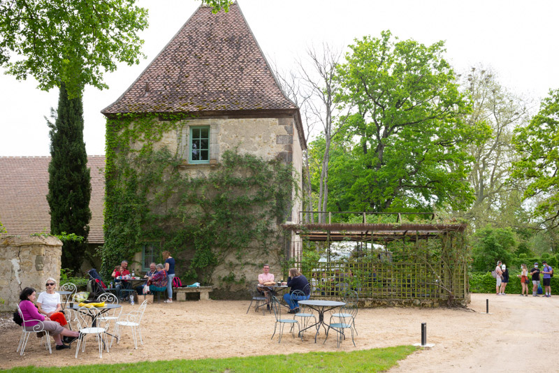 Au Château d'Ainay-Le-Vieil, près de la volière, des gens sont installés pour déjeuner
