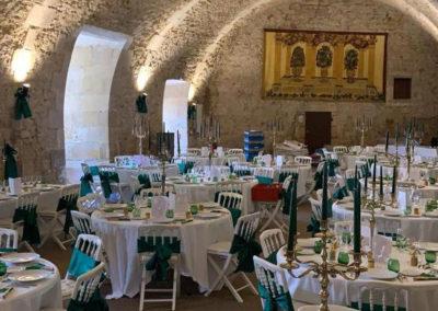 Mariage au château d'Ainay-le-Vieil, les tables rondes du dîner sont dressées dans la salle des archers. Nappes blanches, bougeoirs argentés et détails verts pour un mariage bohème chic