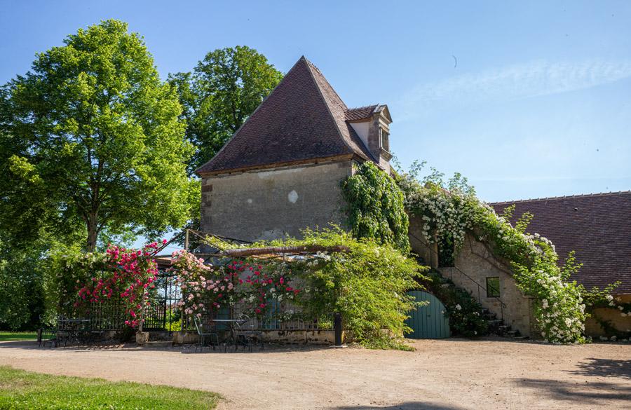 Château d'Ainay-le-Vieil, le pavillon de la volière croulant sous les fleurs des rosiers grimpants