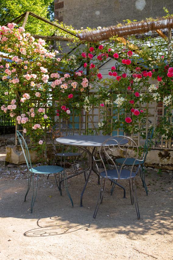 Château d'Ainay-le-Vieil, le pavillon Renaissance dit de la volière, un salon de jardin en métal installé sous les rosiers en fleurs palissés sur les treillages en bois.