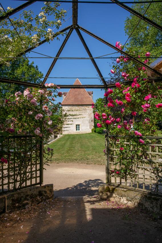 Château d'Ainay-le-Vieil, vue sur le pavillon Renaissance depuis le pavillon de la volière, ciel est bleu, rosiers en fleurs palissés sur les treillages en bois